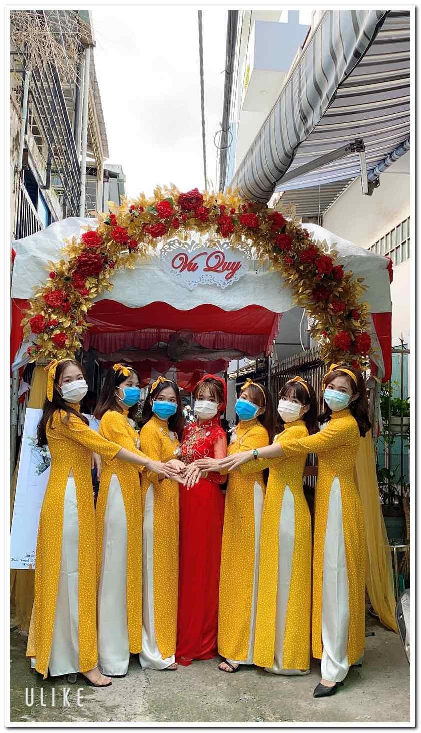 Áo dài bưng quả màu vàng kết hợp rất hợp tông với áo dài cô dâu màu đỏ